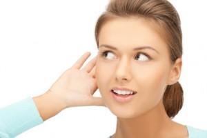 Frau hält ihre Hand ans Ohr, um besser zu hören
